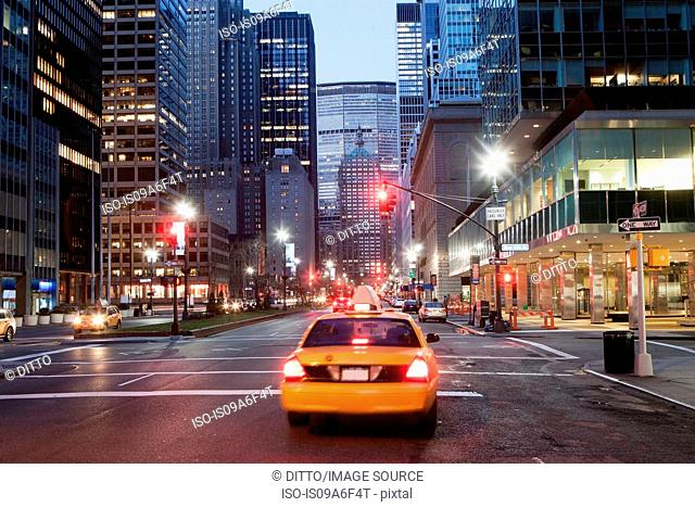 Yellow taxi cab at dusk, New York City, USA