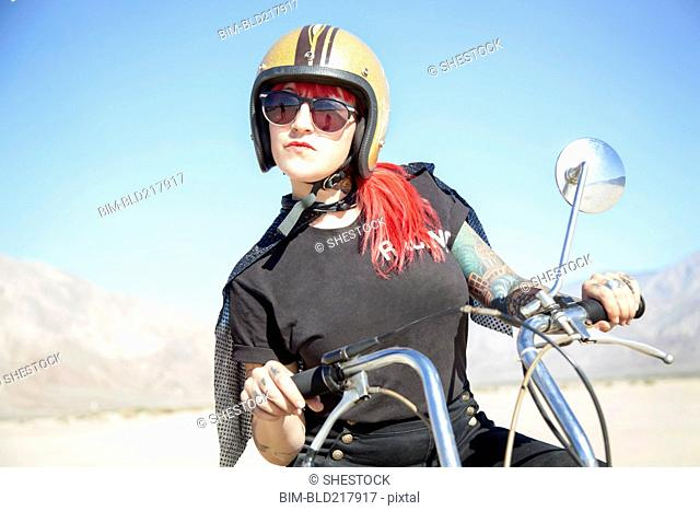 Woman sitting on motorcycle in desert