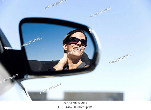Woman passenger in car, reflection in side-view mirror