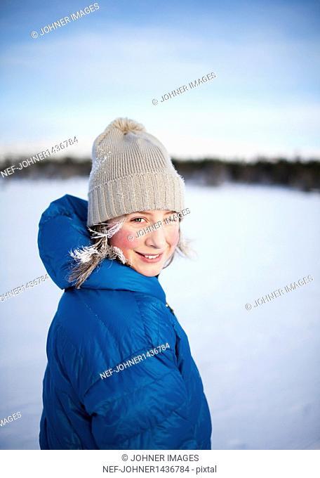 Girl in knit hat winking on snow field