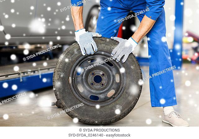 auto mechanic changing car tire at workshop