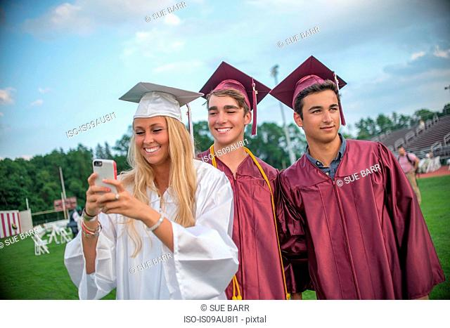 Young female and male graduates taking smartphone selfie at graduation ceremony