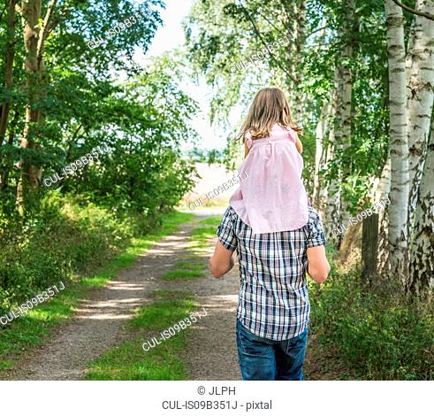 Rear view of father carrying daughter on shoulders, Porta Westfalica, North Rhine Westphalia, Germany