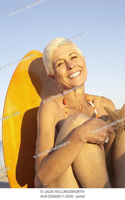 Portrait of a mature woman holding a starfish and smiling