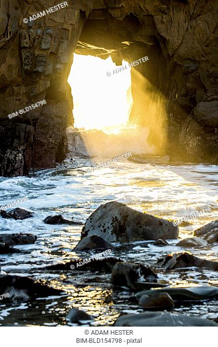 Sunbeam shining through rock formation to ocean waves