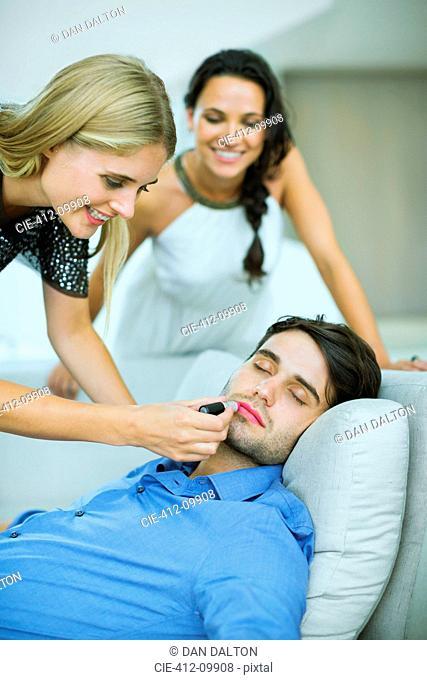 Woman applying lipstick to sleeping man