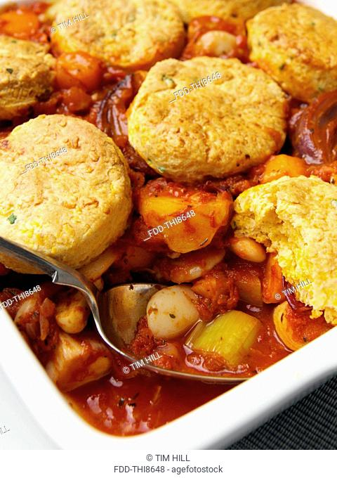 A casserole dish of roast vegetable stew with cobblers