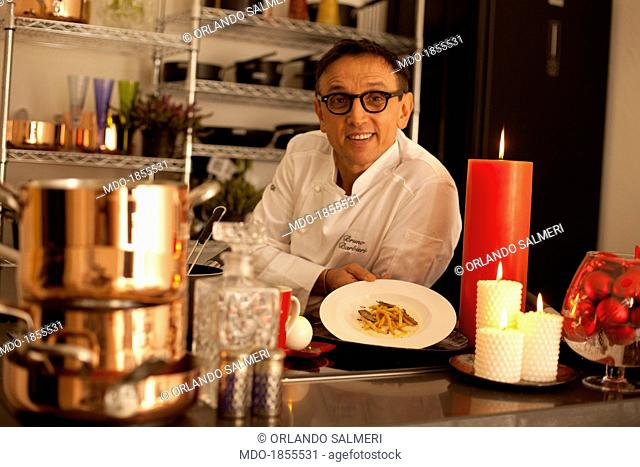 Italian chef awarded with many Michelin stars and judge at the show broadcasted by SkyUno 'Masterchef Italia' Bruno Barbieri leaning on a counter with some...