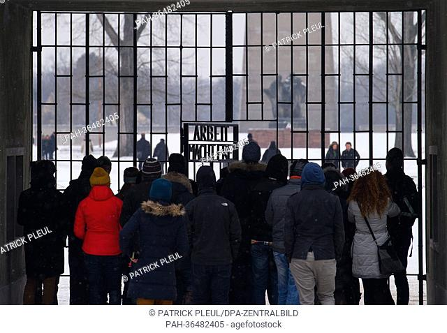 """Visitors stand at the entrance gate with the words """"""""Arbeit macht frei"""""""" at Sachsenhausen Concentration Camp in Oranienburg, Germany, 27 January 2013"""