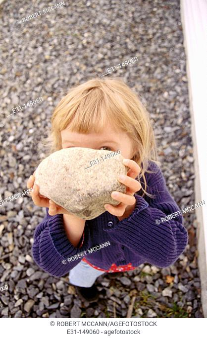 Young girl holding a rock