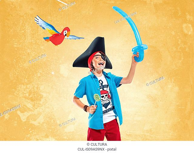 Boy wearing pirate costume and eye patch holding balloon sword and lollipop, looking at camera smiling