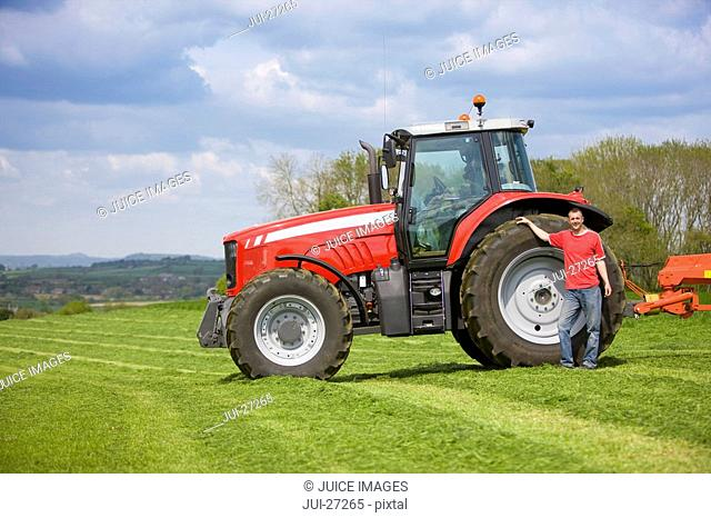 Farmer standing with tractor in silage field
