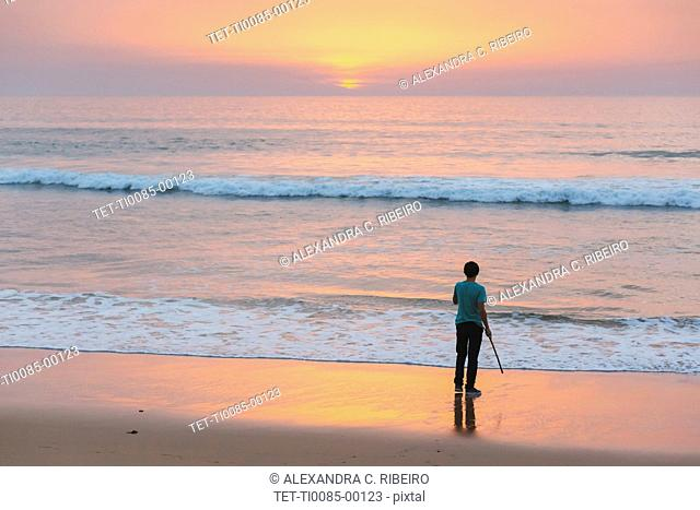 Young man on beach at sunset in Lisbon, Portugal