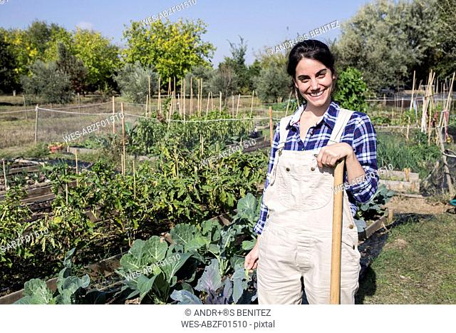 Woman working on farm looking at camera, smiling
