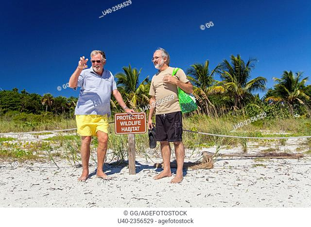 Men standing by beach sign