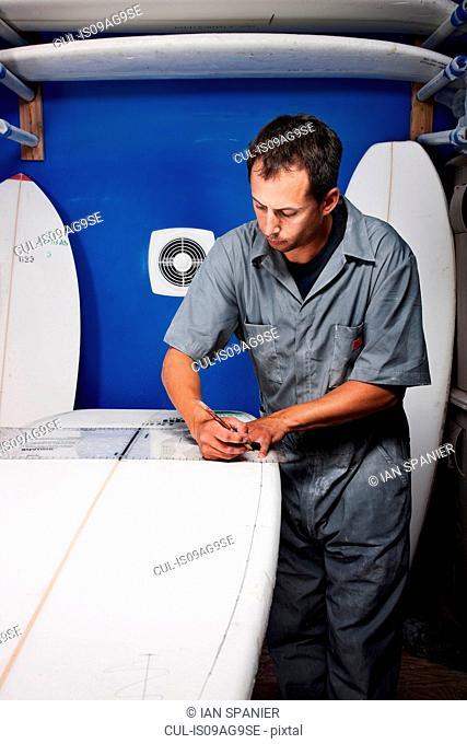 Mid adult man measuring surfboard in his workshop