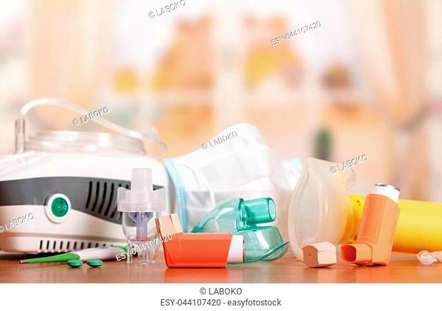 Compressor inhaler and small pocket nebulizer, masks and dispenser for procedure, on blurred light background