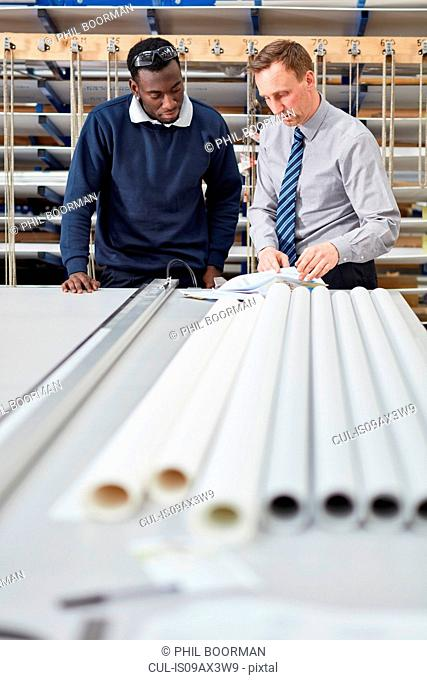 Manager and factory worker checking paperwork in roller blind factory