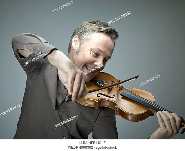 Portrait of smiling man playing violin