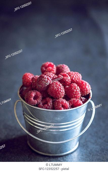 A small metal bucket of freshly picked raspberries