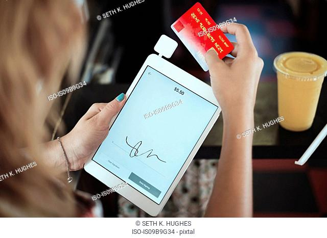 Over shoulder view of young woman holding digital tablet and credit card