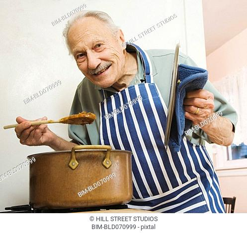 Senior man tasting food in kitchen