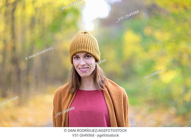 Brunette Woman in Park in Autumnn smiling at camera