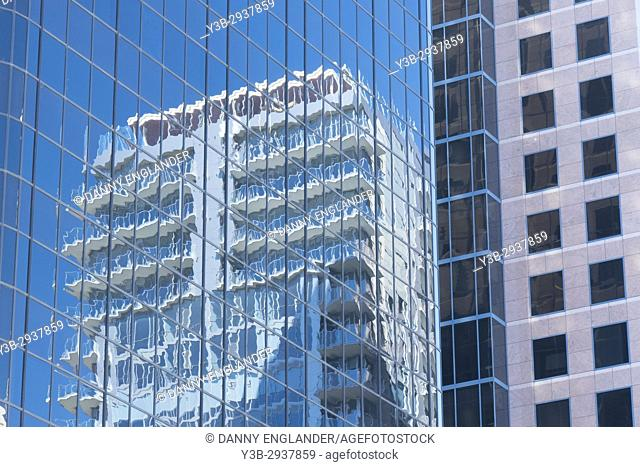 Modern building with a reflection of another high-rise in downtown San Diego, CA
