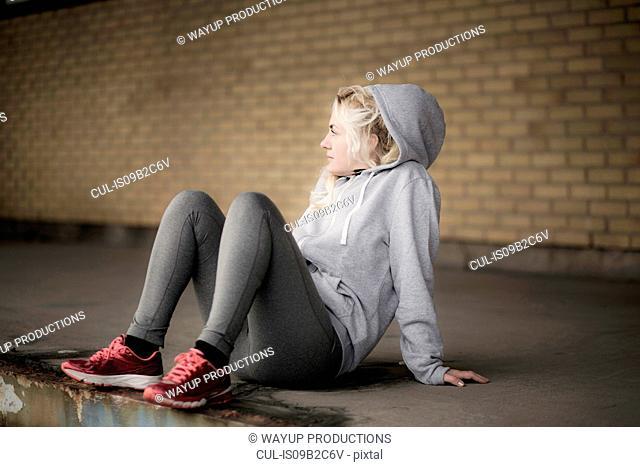 Female runner looking sideways from warehouse platform