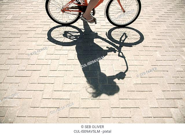 Woman cycling on walkway