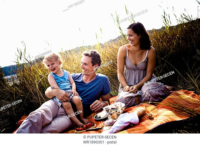 Young family with one child on the lakeside, having a picnic, Bavaria, Germany