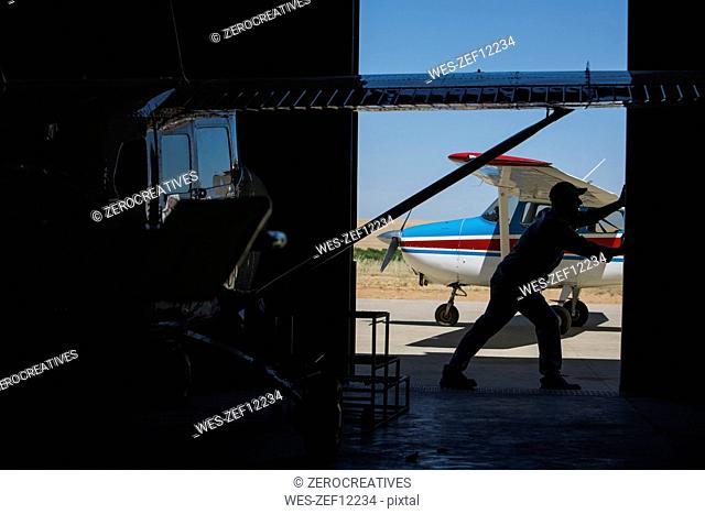 Mechanic opening hangar gate