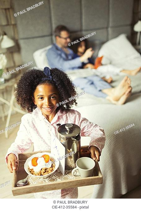 Portrait smiling girl serving Father's Day breakfast in bed to father