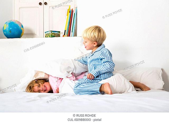 Boy and female twin play fighting on bed