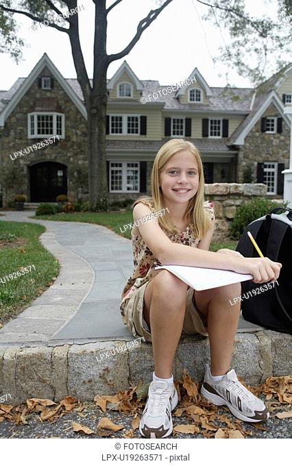 Girl 10-11 doing homework near house, Chatham, New Jersey, USA