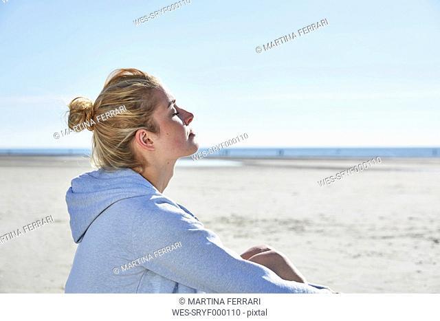 Young woman enjoying the sunshine on the beach