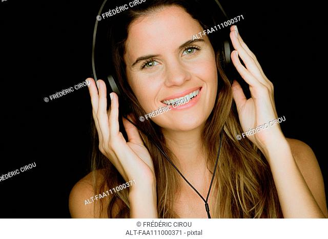 Young woman listening to headphones and smiling cheerfully, portrait