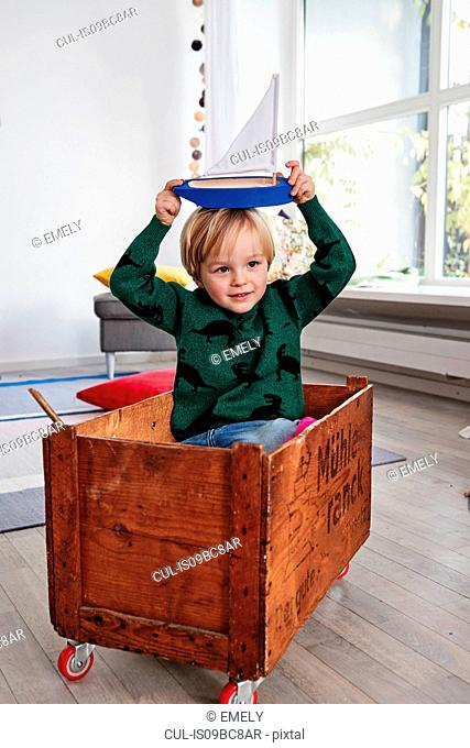 Young boy sitting in toy box, holding toy boat on head