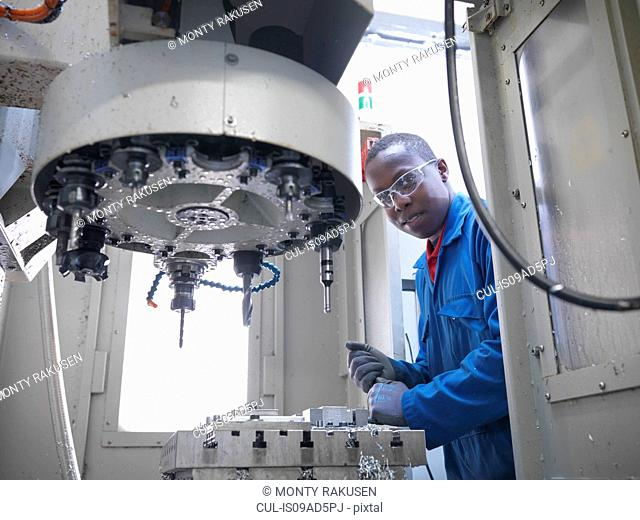 Apprentice engineer using CNC (computer numerical controlled) lathe in factory, portrait