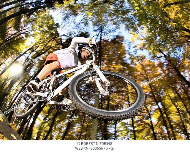 Germany, Bavaria, Landshut, Man riding electric mountain bike in forest