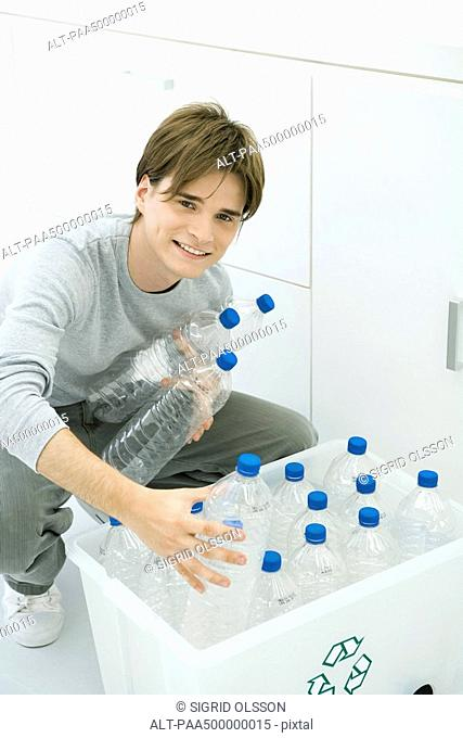Young man putting plastic bottles in recycling bin, smiling at camera