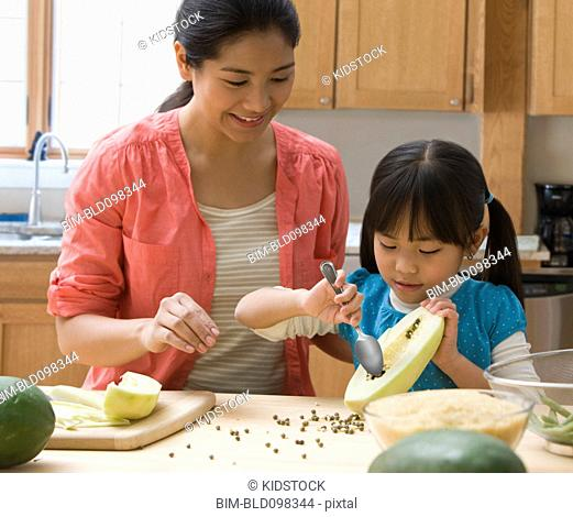 Asian mother and daughter cooking together