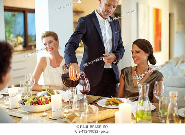 Man pouring wine at dinner party