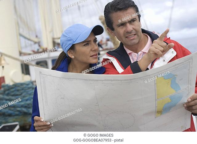 Couple reading a map on ship