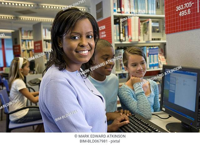 Teacher and students researching in library