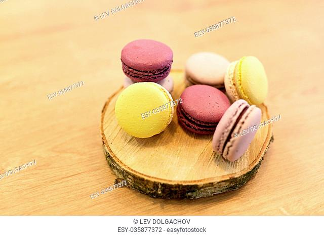 cooking, confectionery and baking concept - different macarons on wooden stand