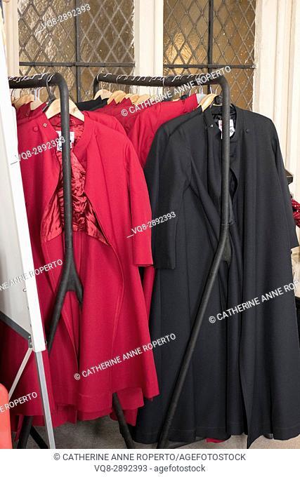 Cerise and magenta choir vestements hung on racks beside diamond leaded glass windows, Bolton, Yorkshire, England, UK