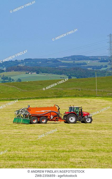 Tractor with tank of liquid fertilising grass. Northumberland England UK