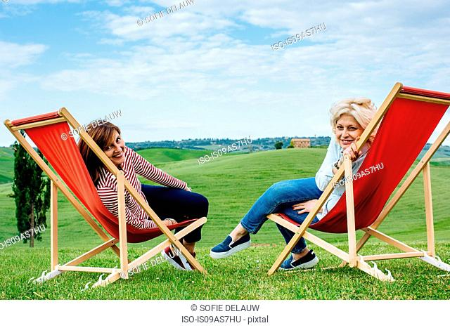 Portrait of two mature female friends sitting on red deck chairs in landscape, Tuscany, Italy