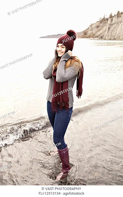 Girl standing in shallow water in autumn at the Scarborough Bluffs wearing a knit hat and scarf; Toronto, Ontario, Canada